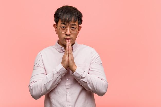 Jovem chinês rezando muito feliz e confiante