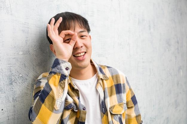 Jovem chinês rosto closeup confiante fazendo okey gesto no olho