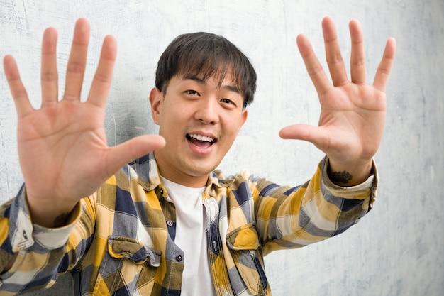 Jovem chinês rosto closeup mostrando o número dez