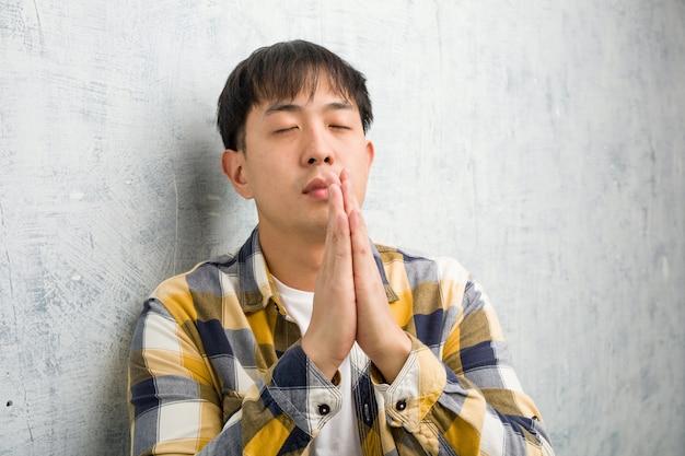 Jovem chinês rosto closeup rezando muito feliz e confiante