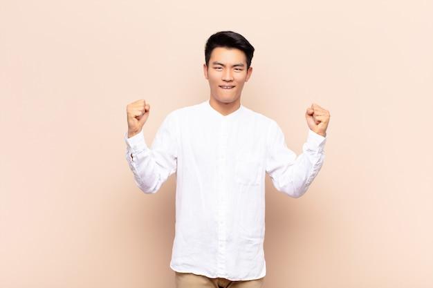 Jovem chinês se sentindo feliz, positivo e bem sucedido, comemorando a vitória, realizações ou boa sorte contra a parede de cores