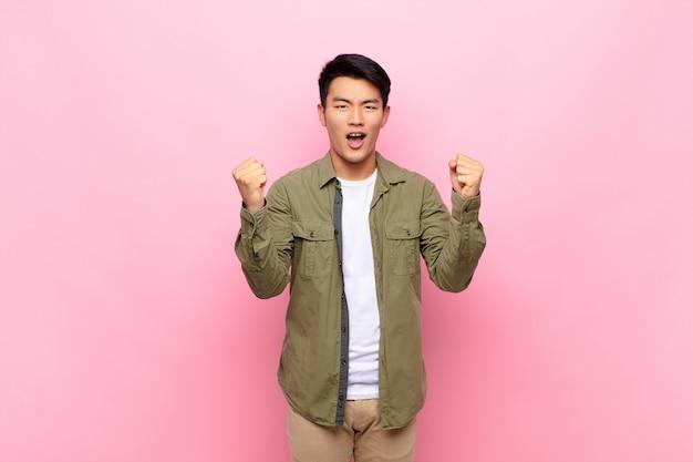 Jovem chinês se sentindo feliz, surpreso e orgulhoso, gritando e comemorando o sucesso com um grande sorriso contra a parede lisa