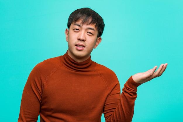 Jovem chinês segurando algo com a mão