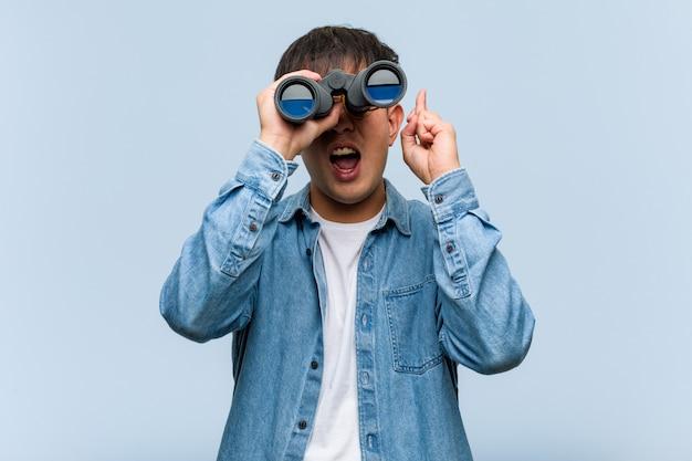 Jovem chinês segurando um binóculo cruzando os dedos por ter sorte