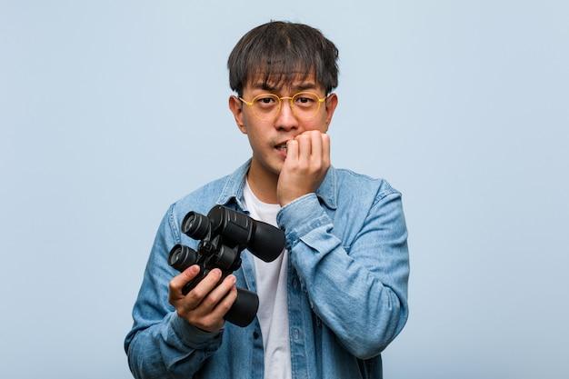 Jovem chinês segurando um binóculo roer unhas, nervoso e muito ansioso