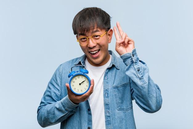Jovem chinês segurando um despertador divertido e feliz fazendo um gesto de vitória