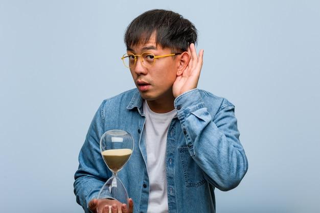 Jovem chinês segurando um temporizador de areia tentar ouvir uma fofoca