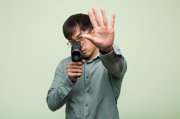 Jovem chinês, segurando um vintage, colocando a mão na frente