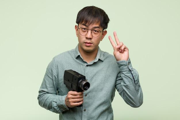 Jovem chinês, segurando uma câmera vintage, mostrando o número dois