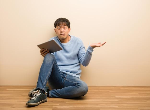 Jovem chinês sentado usando seu tablet confuso e duvidoso