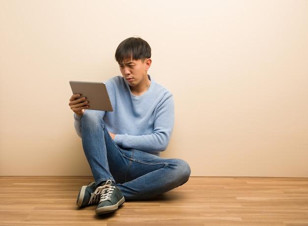 Jovem chinês sentado usando seu tablet cruzando os braços relaxados