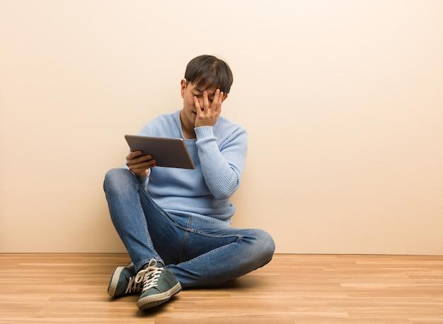 Jovem chinês sentado usando seu tablet, envergonhado e rindo ao mesmo tempo