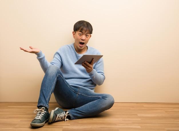 Jovem chinês sentado usando seu tablet segurando algo com a mão