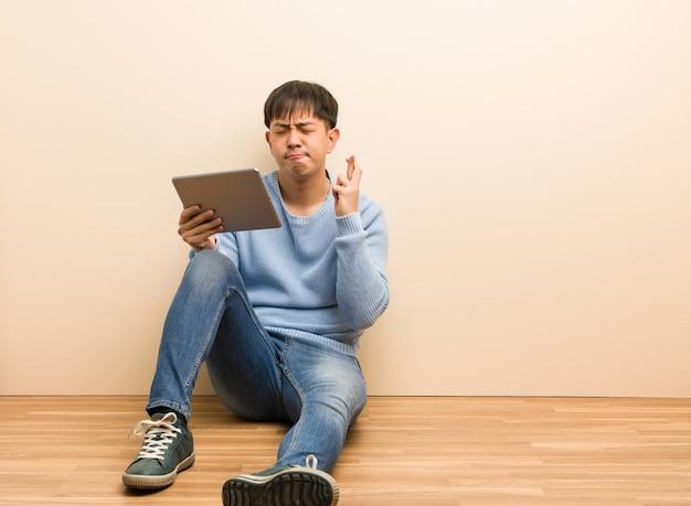 Jovem chinês sentado usando seus dedos de cruzamento de tablet para ter sorte
