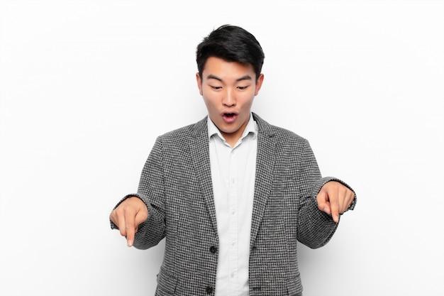 Jovem chinês, sentindo-se chocado, de boca aberta e espantado, olhando e apontando para baixo com descrença e surpresa na parede de cor lisa