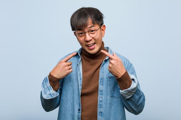 Jovem chinês sorri, apontando a boca