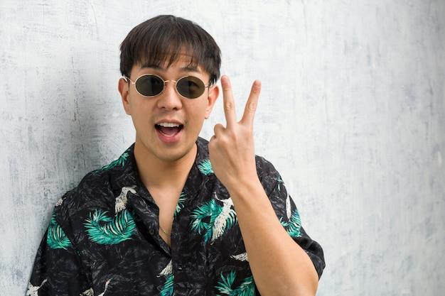 Jovem chinês vestindo roupa de verão divertido e feliz fazendo um gesto de vitória