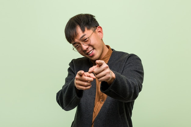 Jovem chinês, vestindo um estilo de roupas legais contra uma parede verde
