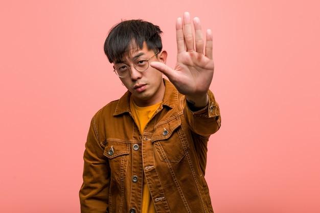 Jovem chinês vestindo uma jaqueta colocando a mão na frente