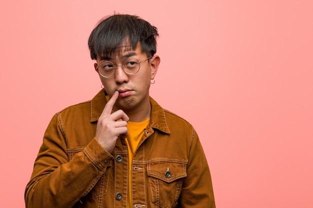 Jovem chinês vestindo uma jaqueta duvidoso e confuso
