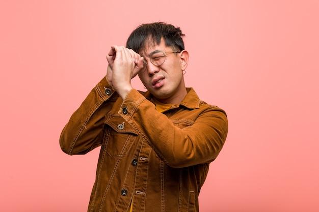 Jovem chinês vestindo uma jaqueta fazendo o gesto de uma luneta