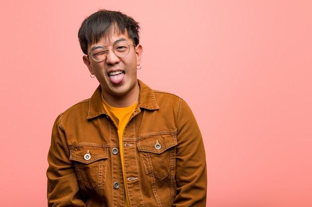 Jovem chinês vestindo uma jaqueta funnny e língua mostrando amigável