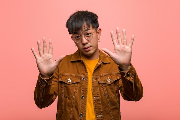 Jovem chinês vestindo uma jaqueta mostrando o número dez