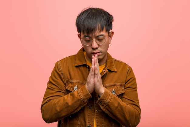 Jovem chinês vestindo uma jaqueta rezando muito feliz e confiante