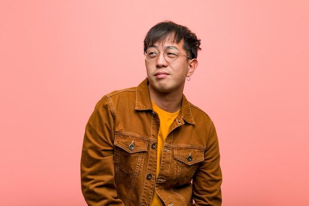 Jovem chinês vestindo uma jaqueta sonhando em alcançar metas e propósitos