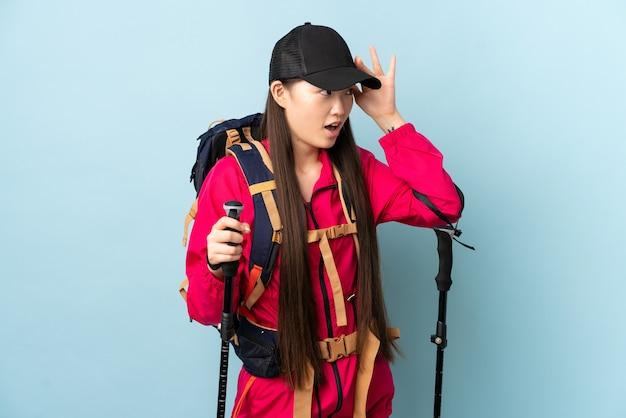 Jovem chinesa com mochila e bastões de trekking em azul isolado com expressão de surpresa ao olhar para o lado