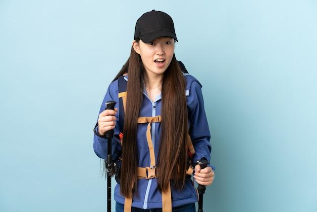 Jovem chinesa com mochila e bastões de trekking em azul isolado com expressão facial surpresa