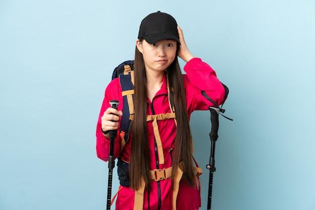 Jovem chinesa com mochila e bastões de trekking em azul isolado com uma expressão de frustração e sem entender