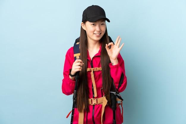 Jovem chinesa com mochila e bastões de trekking em azul isolado mostrando sinal de ok com os dedos