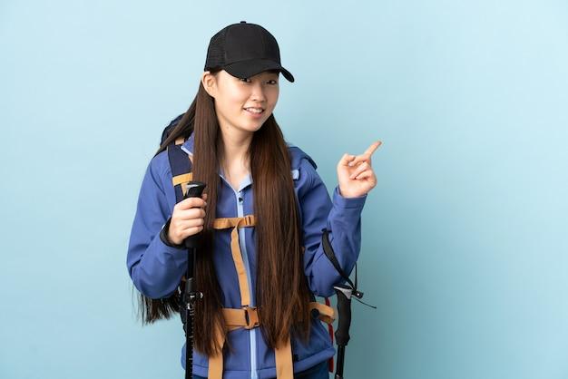 Jovem chinesa com mochila e bastões de trekking isolados apontando para trás