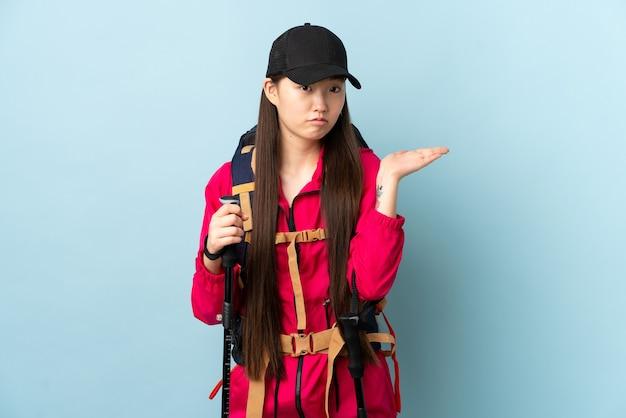 Jovem chinesa com mochila e bastões de trekking isolados