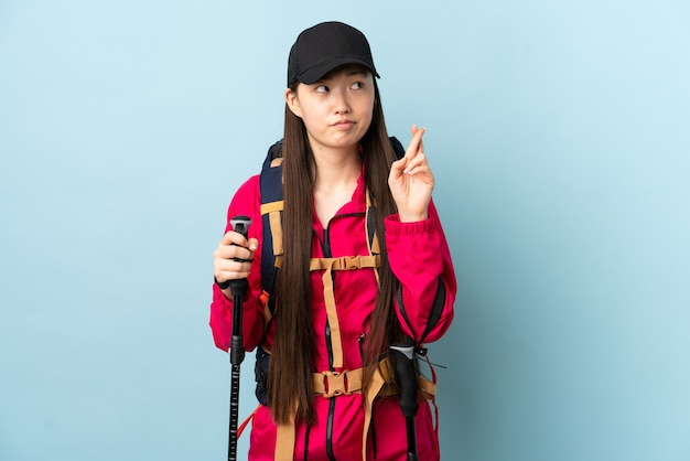 Jovem chinesa com mochila e bastões de trekking na parede azul isolada com dedos se cruzando e desejando o melhor