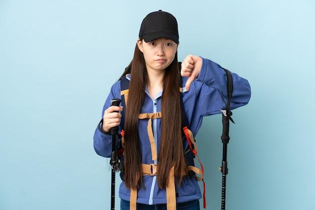 Jovem chinesa com mochila e bastões de trekking na parede azul isolada mostrando o polegar para baixo com expressão negativa