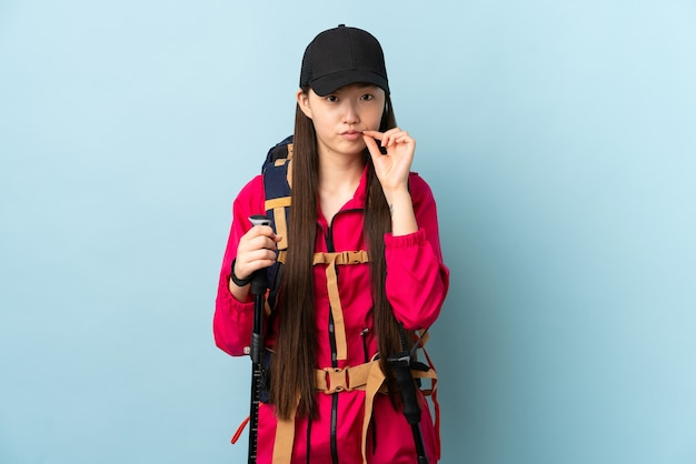 Jovem chinesa com mochila e bastões de trekking na parede azul isolada, mostrando um gesto de silêncio