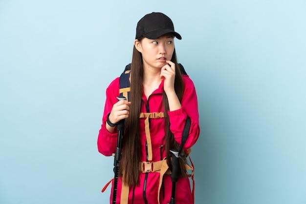 Jovem chinesa com mochila e bastões de trekking na parede azul isolada, nervosa e assustada
