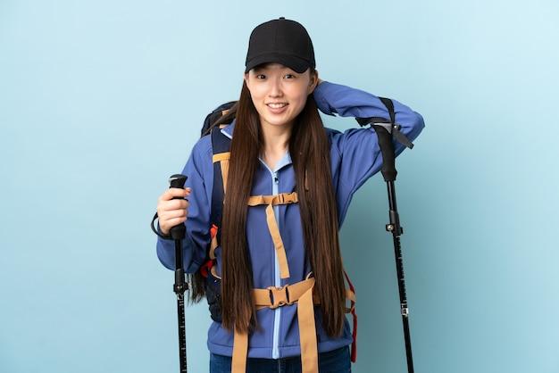 Jovem chinesa com mochila e bastões de trekking na parede azul isolada rindo