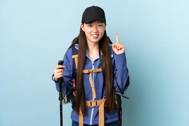 Jovem chinesa com mochila e bastões de trekking sobre azul isolado apontando para uma ótima ideia