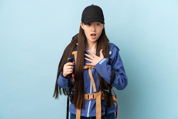 Jovem chinesa com mochila e bastões de trekking sobre azul isolado surpresa e chocada ao olhar para a direita