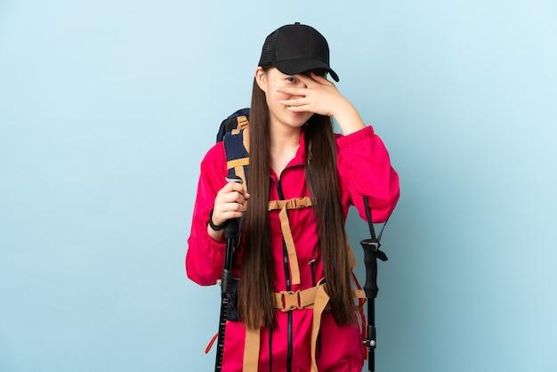 Jovem chinesa com mochila e bastões de trekking sobre fundo azul isolado cobrindo os olhos pelas mãos e sorrindo