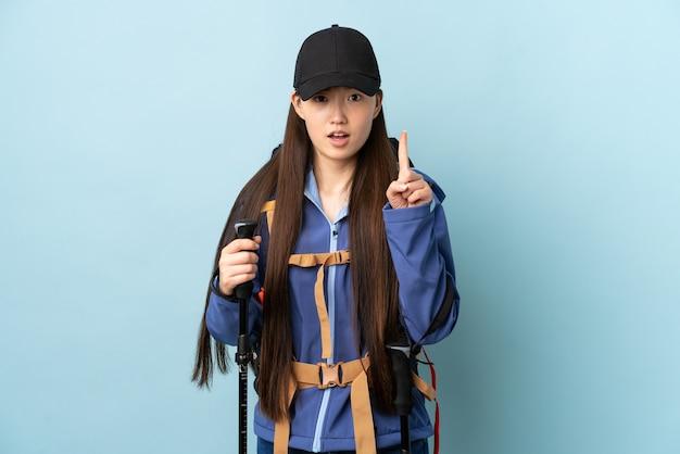 Jovem chinesa com mochila e bastões de trekking sobre o azul, contando um com expressão séria