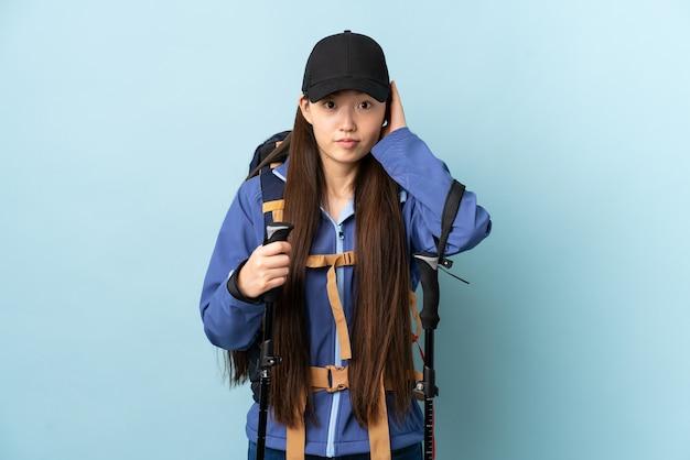 Jovem chinesa com mochila e bastões de trekking sobre o azul isolado frustrada e cobrindo as orelhas