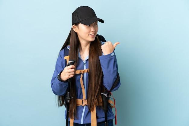 Jovem chinesa com mochila e bastões de trekking sobre parede azul isolada apontando para o lado para apresentar um produto