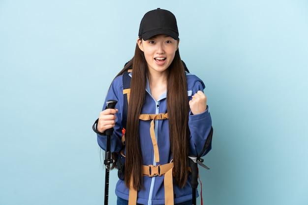 Jovem chinesa com mochila e bastões de trekking sobre parede azul isolada comemorando vitória na posição de vencedora