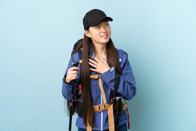 Jovem chinesa com mochila e bastões de trekking sobre parede azul isolada olhando para cima enquanto sorri