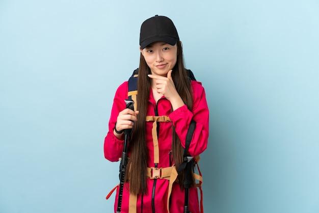 Jovem chinesa com mochila e bastões de trekking sobre parede azul isolada pensando