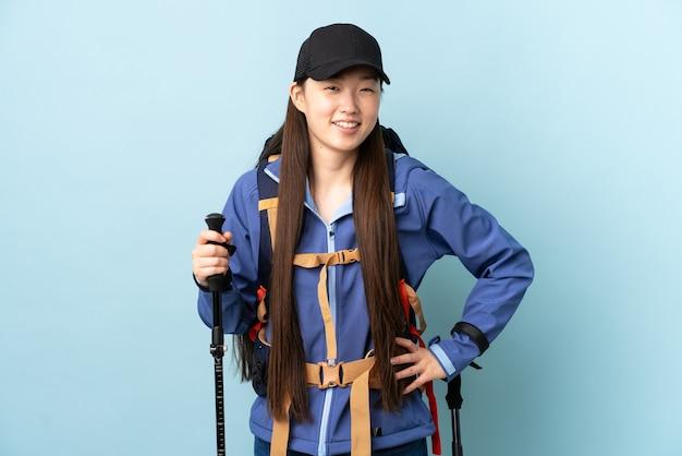Jovem chinesa com mochila e bastões de trekking sobre uma parede azul isolada, posando com os braços na cintura e sorrindo